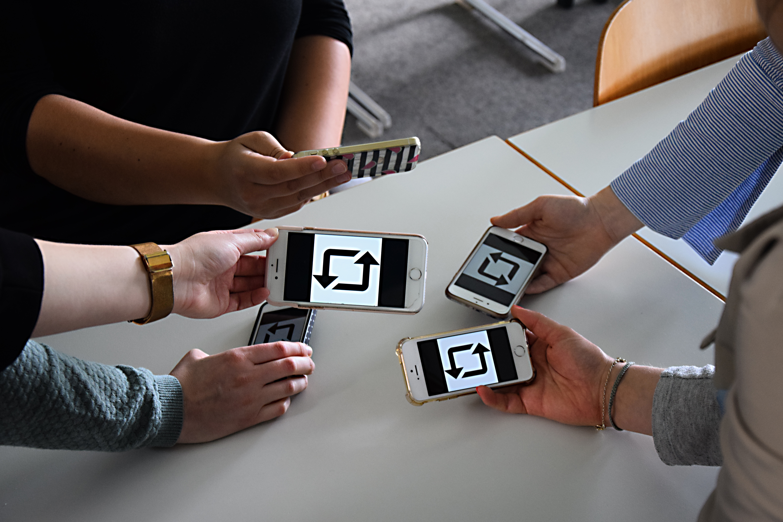 Foto mit mehreren Smartphones. Auf dem Display zu sehen ist das Repostzeichen mit zwei Pfeilen, die einen Kreis formen.