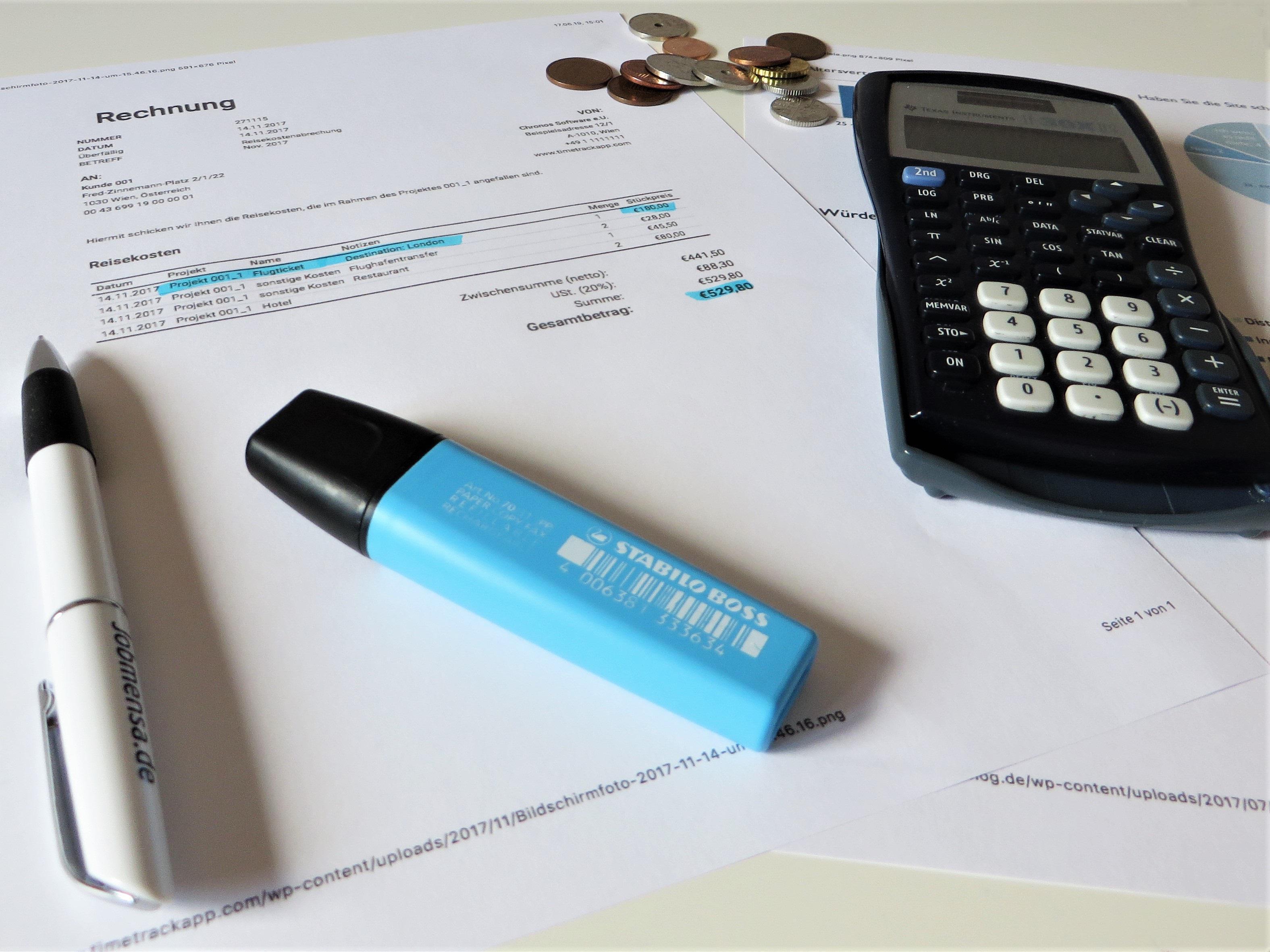 Ein Textmarker liegt auf einem Blatt Papier. Auch ein Taschenrechner und Münzen sind zu sehen.