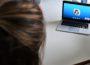 Bild zeigt einen Laptopin der rechten Ecke, geöffnet ist ein Instant-Messenger-Dienst. Links im Bild ist ein Hinterkopf zu sehen, der dem Laptop zugewand ist.