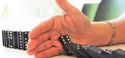 Eine Hand stoppt eine Reihe umfallender Domino-Steine.