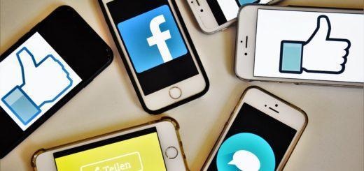 """Mehrere Smartphones liegen auf einem Haufen und zeigen das Facebook-Logo sowie die Symbole für """"Gefällt mir"""", """"Teilen"""" und """"Kommentieren""""."""