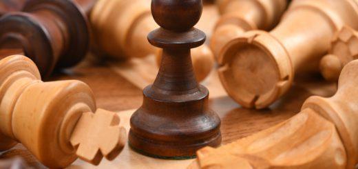 Einige Schachfiguren liegen auf dem Schachbrett und ein Bauer steht im Fokus.