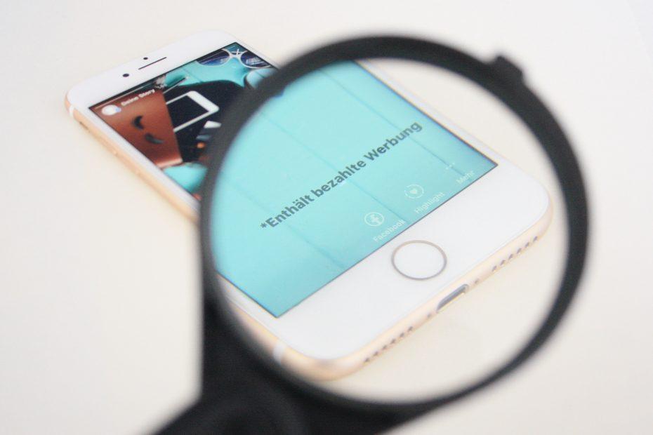 Smartphone mit Lupe und Hinweis bezahlte Werbung